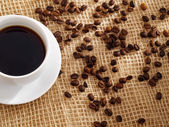 Cup of coffee and roasted coffee beans. — Stock Photo
