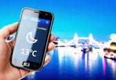 Hand holding smartphone with weather in London — Stock Photo