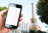 Hand holding smartphone with Paris city view — Stock Photo