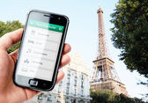 Hand holding smartphone with city guide in Paris — Stock Photo