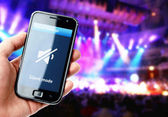 Hand holding smartphone with mute sound during concert — Stock Photo