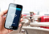 Hand holding smartphone with wi-fi connection in cafe — Stock Photo