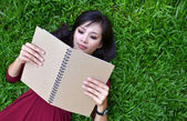Woman lying on green grass with book — Stock Photo