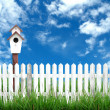 Wooden fence with green grass and blue sky — Stock Photo #27883629