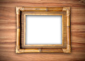 Bamboo frame on wood wall — Stock Photo
