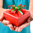 Stock Photo: Womsmile and hold gift box in hands