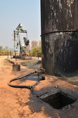 Pumpjack pumping crude oil from oil well — Stock Photo
