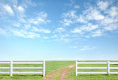 white fence on green grass with blue sky — Photo