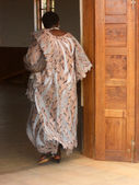 African woman in traditional dress into the church of the Franci — Stock Photo