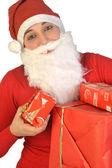 A Santa Claus distributes gifts — Stock Photo