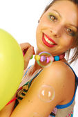 Beautiful girl dynamic and cheerful between balloons and soap bu — Stock Photo