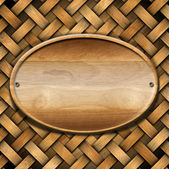 Oval Wood Board on Braided Wooden Background — Stock Photo