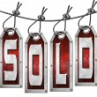 Sold Tags Hanging on White Background - Stock Photo