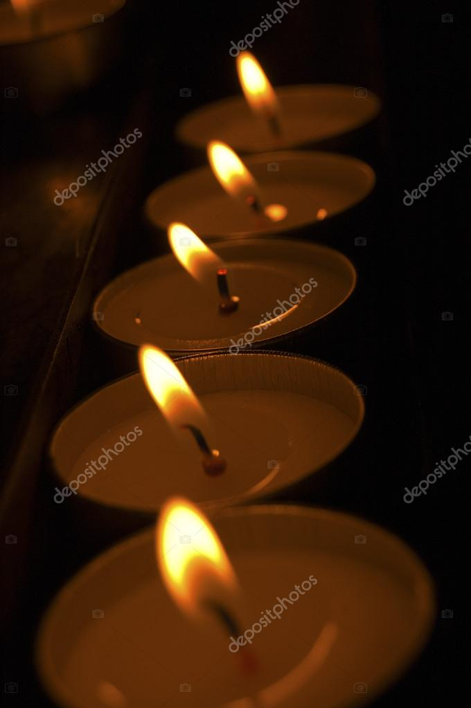 A group of warm glowing candles on black background  Stock Photo #13895542
