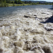 Brown River Rapids and Blue Sky - Stock Photo