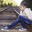 Girl sitting on railway — Stock Photo