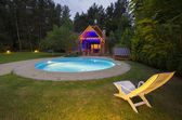 A waterpool with chair near wooden house at night — Stock Photo