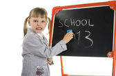 Little girl teaching near board in studio — Stock Photo