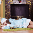 Nice teen girl sleeping near fireplace — Stock Photo