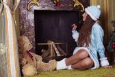 Snow-maiden looking into fireplace chimney — Stock Photo