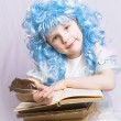 Little girl with blue hair writing a book — Stock Photo #18506471