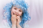Little girl with blue hair eating cookie — Stock Photo
