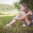 Cute teenage girl sitting on the grass — Stock Photo
