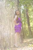 柳細工のフェンスに近い紫のドレスで素敵な女の子 — ストック写真