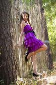 Nice girl in violet dress near wicker fence — ストック写真