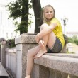 Stock Photo: Child kid girl taking rest near fountain
