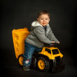 Постер, плакат: Young boy playing on toy dump truck