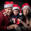 Couple holding their son at christmas — Stok fotoğraf