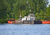 Um rebocador auxiliando uma barcaça — Foto Stock