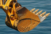 Rusty bulldozer scoop over water — Stock Photo
