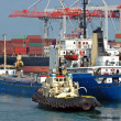 Stock Photo: Tugboat assisting bulk cargo ship
