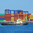 Stock Photo: Container stack and tugboat