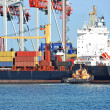 Tugboat assisting container cargo ship — Stock Photo