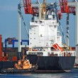 Стоковое фото: Tugboat assisting container cargo ship