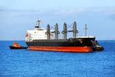 Tugboat assisting bulk cargo ship — Stock Photo