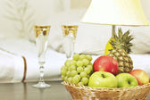 Fruit and glasses on table in interior — Stock Photo