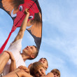 Family from four against the blue sky flying kite. — Stock Photo