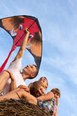 Famille de quatre contre le ciel bleu volant cerf-volant. — Photo