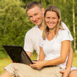 The couple outdoors has rest with the laptop - Stock Photo