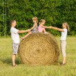 Happy family with child on haystack in sunny day — Stock Photo