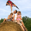 Stock Photo: Happy family astride hay flying kite.