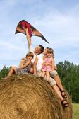 The happy family astride hay flying kite. — Stock Photo