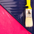 Red paint with yellow brush in tray. Top view. — Stock Photo