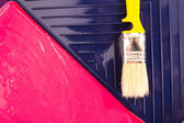 Red paint with yellow brush in tray. Top view. — Foto Stock