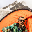 Stock Photo: Rescuer in mountains talks on handheld transceiver