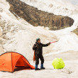 The climber standing near tent on glacier — Stock Photo